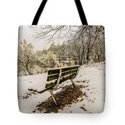 Park Bench In The Snow Covered Park Overlooking Lake Tote Bag