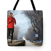 A Woman Running Near A Railroad Track Tote Bag
