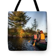 A Young Couple Paddles A Canoe On Long Tote Bag