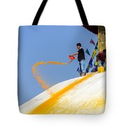 Man Throwing Orange Paint On Boudhanath Stupa Tote Bag