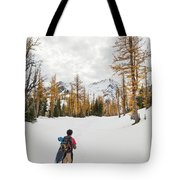 A Backpacker Hikes Through Snow Tote Bag