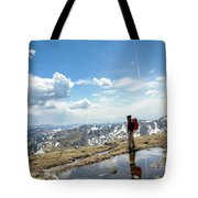 A Backpacker Stands Atop A Mountain Tote Bag
