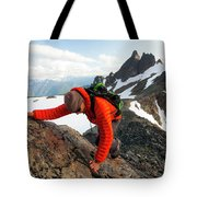 A Climber Scrambles Up A Rocky Mountain Tote Bag