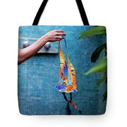 A Female Hand Holding A Bathing Suit Tote Bag