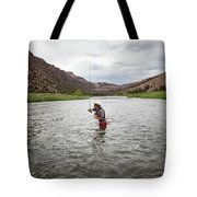 A Fly Fisherman Mends While Fishing Tote Bag