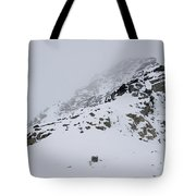 A Hiker Approaches A Snowy Peak Covered Tote Bag