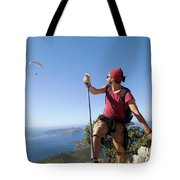 A Male Climber Looking At Paragliding Tote Bag