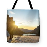 A Man Hiking On Snowfield At Sunrise Tote Bag