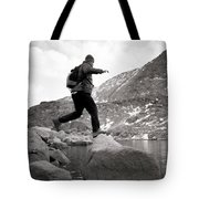 A Man Jumps From One Rock To Another Tote Bag