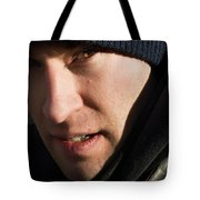 A Man Looks Up After Examining Tote Bag