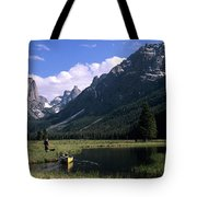 A Man Pulls His Canoe Up A River Valley Tote Bag