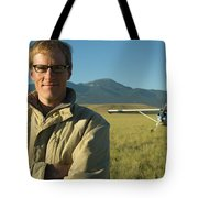 A Man Stands In A Field Next Tote Bag