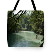 A Man Stands In A River Wearing Waders Tote Bag
