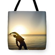 A Person Practices Yoga At The Waters Tote Bag