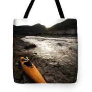 A Whitewater Kayak Rests On The Shore Tote Bag