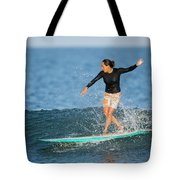 A Woman Rides A Wave On A Longboard Tote Bag