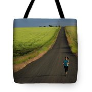 A Woman Running On A Dirt Road Tote Bag