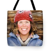 A Woman Stands Against A Log Cabin Tote Bag