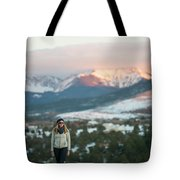 A Woman Stands Against A Snowy Mountain Tote Bag