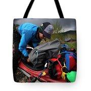 A Woman Unloads Her Kayak Tote Bag