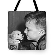 A Young Boy Is Face To Face With A Puppy Tongue. Tote Bag