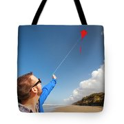 A Young Man Looks Up At His Red Kite Tote Bag