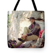 A Young Rock Climber Puts On A Climbing Tote Bag