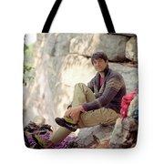A Young Rock Climber Puts On A Climbing Tote Bag