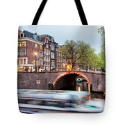 Canal Bridge And Boat Tour In Amsterdam At Evening Tote Bag