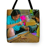 Child Watches As Mom Works In Teak Wood Carving Shop In Kanchanaburi-thailand Tote Bag