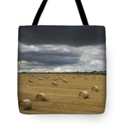 Dark Storm Clouds Over A Field With Hay Tote Bag