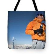 Dressed In Orange, A Skier Sips A Warm Tote Bag