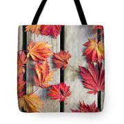 Japanese Maple Tree Leaves On Wood Deck Tote Bag by David Gn