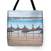 Straw Umbrellas On Empty Beach Tote Bag