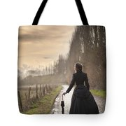 Victorian Woman Walking On A Cobbled Avenue At Sunset Tote Bag