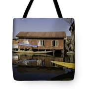 Yellow Shikara In Front Of A Run Down Area Of Houses In The Dal Lake Tote Bag