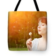 Young Beautiful Woman Blowing A Dandelion In Spring Scenery Tote Bag