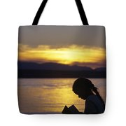 Young Girl Silhouetted Reading A Book On The Beach At Sunset Tote Bag