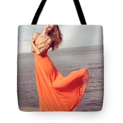 Young Woman In Orange Dress Flying In The Wind At Sea Shore Tote Bag