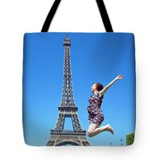 Young Woman Jumping Against Eiffel Tower Tote Bag