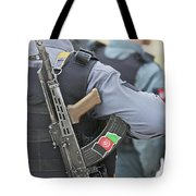 An Ak-47 Rests On The Sling Of An Tote Bag