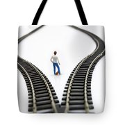 Figurine Between Two Tracks Leading Into Different Directions Symbolic Image For Making Decisions. Tote Bag