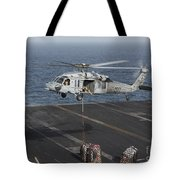 A Mh-60s Knighthawk Conducts A Vertical Tote Bag
