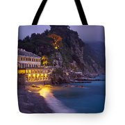 A Building Illuminated At Night Along Tote Bag