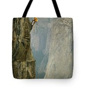 A Climber Makes His Way Up A Rock Face Tote Bag