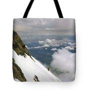 A Climber Walks Along A Steep Slope Tote Bag