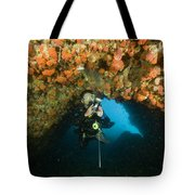 A Diver Explores A Cavern With Orange Tote Bag