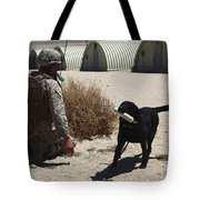 A Dog Handler Calls Over A Black Tote Bag by Stocktrek Images