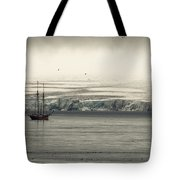 A Double-masted Sailboat Floats Near An Tote Bag