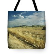 A Hay Field With Bales Sitting Tote Bag